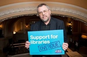 Alan Gibbons holding Support for Libraries Overdue sign, with Westminster Hall in background